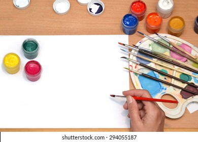 workplace painter, brush in hand, jars with gouache, canvas for painting, palette, the background art