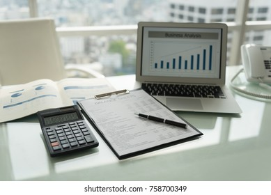 Workplace. The pen on balance sheet report with calculator, laptop computer showing business graph for analysis performance of operation.
