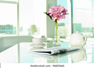 Workplace with porcelain cup and pot, newspaper and bunch of flowers