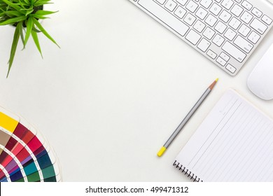 Workplace of professional Designer on white Office Table with color palette multiple colored gamma Notepad Pen Computer and green Plant