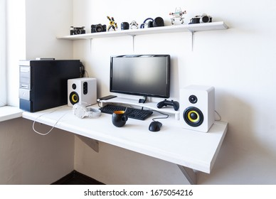 The workplace of a professional gamer with a monitor, gamepad, headphones and an armchair.