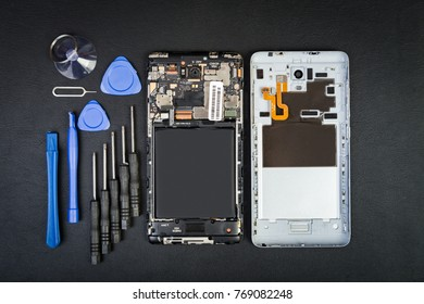 Workplace of the repairman with the  phone and special purpose tools on the black table. Disassembled smartphone in flatlay style.