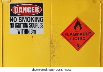 Workplace safety signs on a yellow cabinet displaying danger flammable liquid and no flame text. OHS WHS workplace occupational health and safety concept.