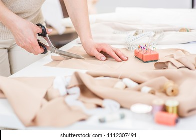 Workplace of seamstress. Close up dressmaker cuts dress detail with scissors