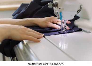 Workplace of seamstress. Close up of sewing Process. Fashion designer working in atelier.