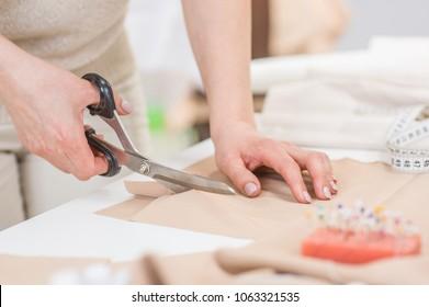 Workplace of seamstress. Dressmaker cuts dress detail with scissors