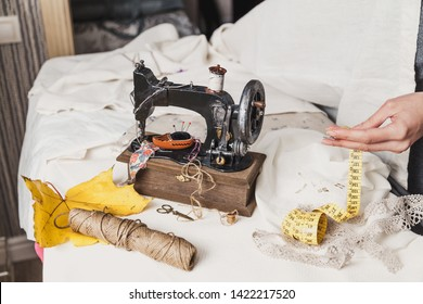 Workplace seamstress. Vintage sewing machine and a skein of threads. A yellow maple leaf lies next to it. The woman's hands fold a flexible tape