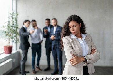 Workplace Sexism And Bullying. Unhappy Victimized Businesswoman Standing While Her Male Colleagues Whispering Behind Her Back Standing In Modern Office. Corporate Problems, Female Rights Concept