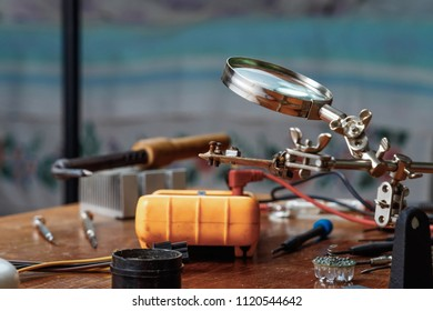 Workplace with soldering iron, microcircuit, magnifying glass, magnifying glass, measuring instruments. Electronics repair, master.