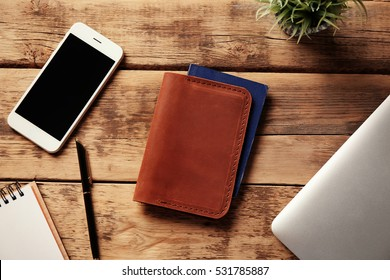 Workplace with stylish leather passport cover and smartphone