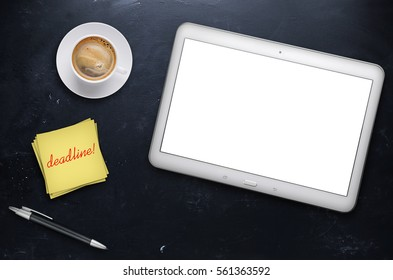Workplace with tablet and cup of coffee on black table.