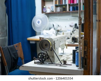 workplace of tailor seamstress needlewoman. old fashioned vintage sewing machine and empty chair