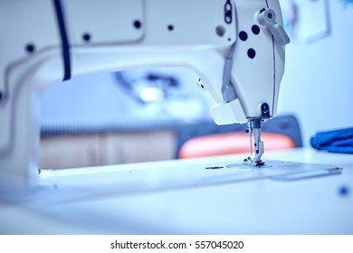 Workplace of tailor - sewing machine, rolls of of thread, fabric, scissors.