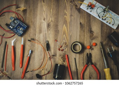 Workplace With Tools: Breadboard, Push Button, Resistors, Tweezers, Nippers, Soldering Iron, Wires, Microcircuit, Lamp Socket. Electronics Repair Service. Concept of  Electronics, Programming.