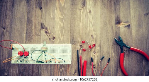 Workplace With Tools: Breadboard, Push Button, Resistors, Tweezers, Nippers, Wires. Electronics Repair Service. Concept of  Electronics, Programming. Long Banner With Open Space For Text.