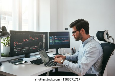 Workplace of trader. Young bearded trader wearing eyeglasses using his laptop while sitting in office in front of computer screens with trading charts and financial data