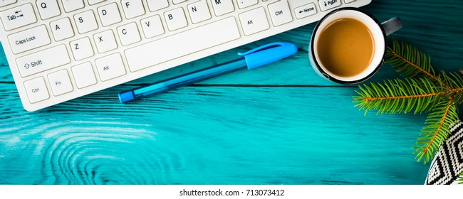 Workplace winter background with keayboard, notebook and coffee on dark green wooden background and green branch. Online blog concept