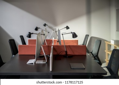 Workplaces in an ofice with gray walls. There are dark tables with peach partitions and computers, black chairs, wooden shelves with books, luminous lamps. Horizontal.