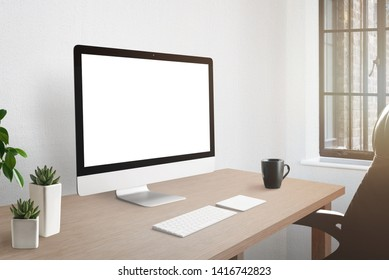 Workroom desk with computer display with isolated screen for mockup. Plants and cup of coffee beside.