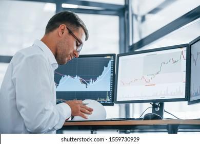 Funktioniert mit Dokumenten. Junge Geschäftsleute in formaler Kleidung sind im Büro mit mehreren Bildschirmen. Konzeption von Austausch und Geld.