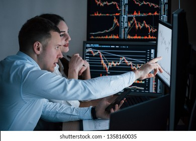 Works at evening. Team of stockbrokers are having a conversation in a office with multiple display screens.