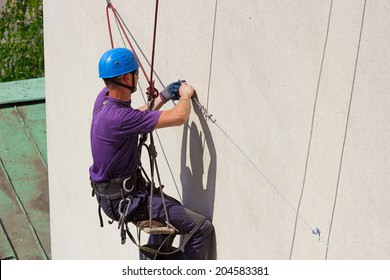 Works on skyscraper  ; Specially equipped worker performs height work,photography