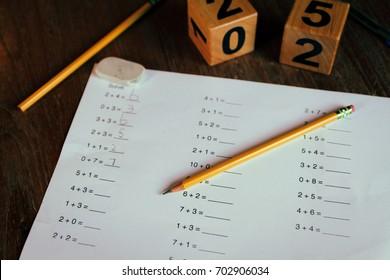 Worksheet for 1st grade math homework with pencils and eraser on the wooden desk.