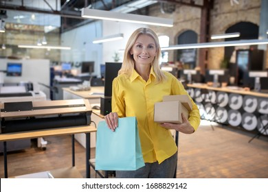 At workshop. Blonde woman holding boxes and paper packege, smiling