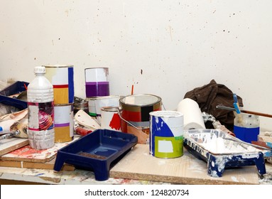 Workshop with different paint cans and other painting equipment