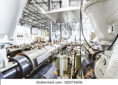 Workshop with extruders for producing plastic pipes. High speed extrusion line of water suppply and gas pipe. Manufacturing facility.