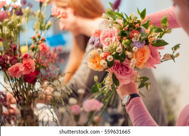 Workshop florist, making bouquets and flower arrangements. Woman collecting a bouquet of roses. Soft focus