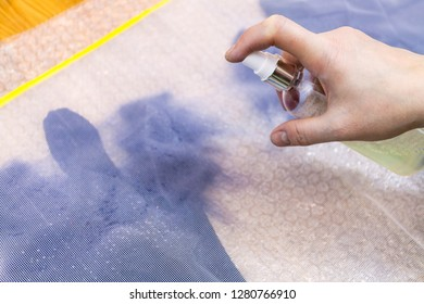 workshop of hand making a fleece gloves from blue Merino sheep wool using wet felting process - craftsman damping fibers on cutting pattern of fingers through plastic mesh by spray