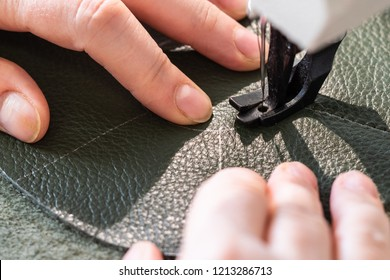 workshop of making the leather bag for jewelry - craftsman sews pockets of pouch on sewing machine