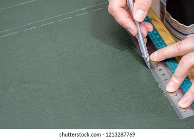 workshop of making textile and leather travel bag - craftsman draws the pattern on green leather using ruller