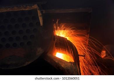 The workshop welder cuts metal, forming an orange spark