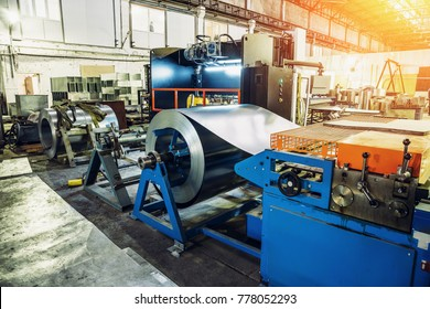 Worksop with machinery tools and equipment, rolls of galvanized steel for production metal pipes and tubes for industrial ventilation systems in factory, toned