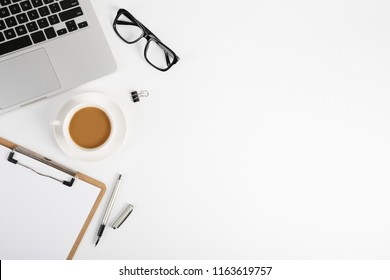 Workspace with blank clip board, laptop keyboard, office supplies, pen, glasses and coffee cup on white background. Flat lay, top view office table desk.