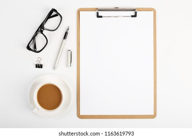Workspace with blank clip board, office supplies, pen, glasses and coffee cup on white background. Flat lay, top view office table desk.