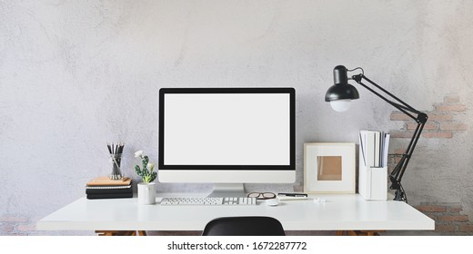 Workspace blank screen Computer and Equipment on table and loft wall background.