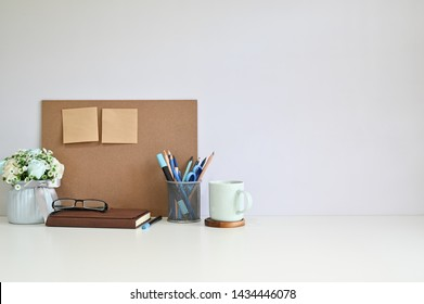 Workspace board and sticky note, coffee with office supplies on table copy space.
