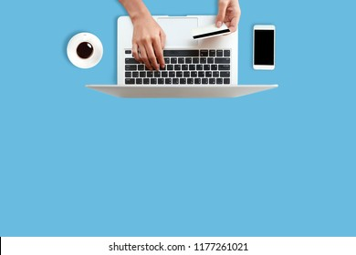 workspace business desk with coffee cup, smart phone, credit card and human hand using computer on blue desk (idea for shopping and online payment)