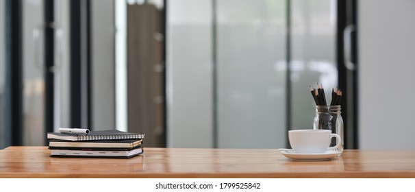 Workspace coffee cup and pencil holder are putting on desk surrounded by a stack of books and a pen.
