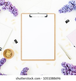 Workspace composition with clipboard, notebook, pen, lilac and accessories on white background. Flat lay, top view. Beauty blog concept. Blogger of freelancer