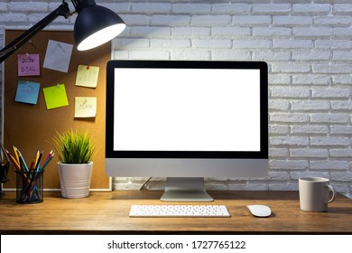 workspace with computer with blank white screen mockup, and office supplies on a wooden desk