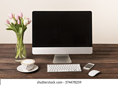 Workspace with computer at home or in the studio , a desk with flowers.