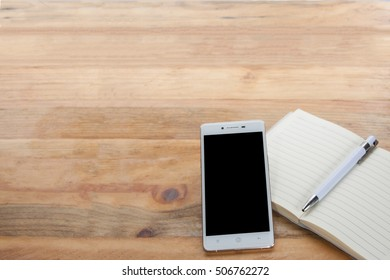 workspace desk blank notebook pen copy space and mobile phone on wooden background.