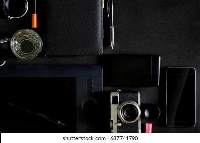 Designer's Workspace desk, Old cameras and tools for creative or graphic designer stuff on dark table.