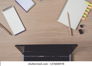 Workspace with diary or notebook and clipboard, laptop, mouse computer, keyboard, pencil, pen, sticky notes on wooden background. Flat lay, top view office table desk and copyspace