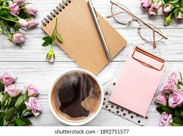 Workspace with diary, notebook, clipboard, roses on white background. Home office desk. Top view feminine background. Flat lay, top view.