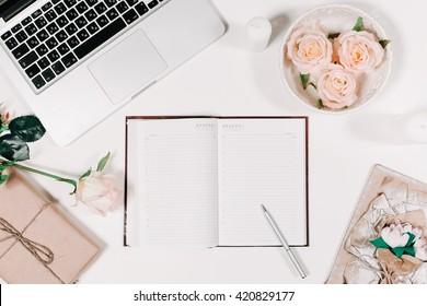 WorkSpace mit Tagebuch, Stift, Vintage-Tablett, rosafarbene Rose, Geschenk in Pergament auf weißem Hintergrund. Draufsicht, flacher Hintergrund